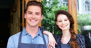 Waiter and waitresses standing at the entrance of café stock footage