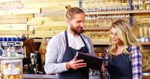 Waiter and waitresses using digital tablet at counter stock footage
