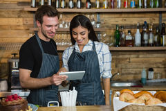 Waiter and waitresses using digital tablet at counter Stock Photos