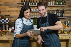 Waiter and waitresses using digital tablet at counter Royalty Free Stock Images