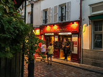 Waiter waits for customers at Chez ma Cousine on Montmartre in Paris. Waiter stands at door of Paris cafe hoping to draw in tourists; Montmartre, Paris, France Royalty Free Stock Images