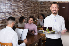 Waiter welcoming guests in restaurant. Positive male waiter showing rustic restaurant to visitors Royalty Free Stock Photography