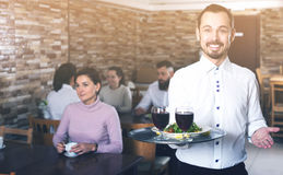 Waiter welcoming guests in restaurant. Positive male waiter welcoming guests to rustic restaurant Royalty Free Stock Images