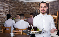 Waiter welcoming guests in restaurant. Smiling men waiter demonstrating country restaurant to visitors Stock Image