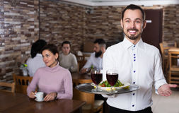 Waiter welcoming guests in restaurant. Young male waiter showing rustic restaurant to visitors Stock Photos