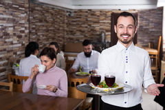 Waiter welcoming guests in restaurant. Young men waiter demonstrating rustic restaurant to visitors Royalty Free Stock Photo