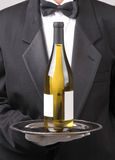 Waiter with White Wine Bottle Blank Label. Close up of a Waiter holding chardonnay wine bottle on silver tray vertical format torso only Royalty Free Stock Photo