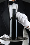 Waiter With Wine Bottle on Tray. Closeup of a waiter wearing a tuxedo and white gloves holding a wine bottle on a serving tray. Vertical format. The man is Royalty Free Stock Images