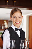 Waiter with wine glasses in hotel stock images