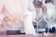 The waiter wipes the wine glasses. The bartender wipes the wine glasses. The waiter wipes the wine glasses. The bartender cleans the glass. Focus on the wine Royalty Free Stock Images