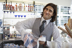 Waiter wiping glass with dishtowel behind bar, smiling, portrait (blurred motion) Royalty Free Stock Images
