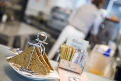 Waiter working in cafe, focus on toast rack in foreground, close-up (tilt) Stock Photo