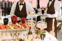 Waiters with the alcohol drinks and fruits Stock Image