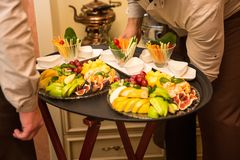Waiters carrying tray with plates with fruits and vegetables on some festive event Stock Images