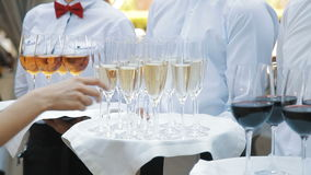 Waiters greet guests with alcoholic drinks. Champagne, red, white wine on trays stock video