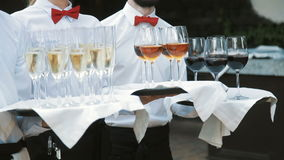 Waiters greet guests with alcoholic drinks. Champagne, red, white wine on trays stock footage