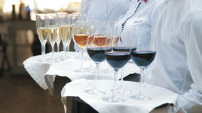 Waiters greet guests with alcoholic drinks. Champagne, red, white wine on trays stock video footage