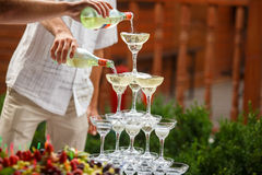 Waiters pour champagne on a pyramid of wineglasses.  Royalty Free Stock Image