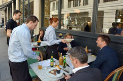 Waiters serving food and drinks to people dining in a restaurant Stock Photo