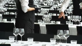 Serving in the Restaurant. The waiters are serving the tables before the reception in the restaurant stock footage