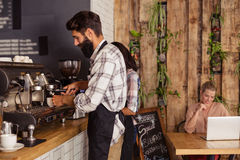 Waiters using a coffee machine and customer on a laptop Royalty Free Stock Photography