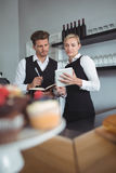 Waiters using digital tablet at counter Royalty Free Stock Photography