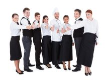 Waiters and waitresses showing thumbs up sign. Isolated on white background Stock Photo