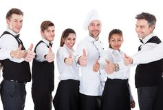 Waiters and waitresses showing thumbs up sign. Isolated on white background Royalty Free Stock Images