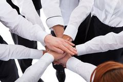 Waiters and waitresses stacking hands Stock Image