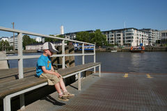 Waiting for... A boy waiting for a ferry on the bank of the river Aurajoki in Turku Royalty Free Stock Image