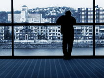 Waiting. Man looking out window into city on riverbank stock photography