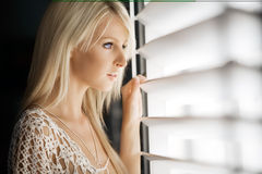 Waiting. Beautiful young woman looks out through blinds Stock Images