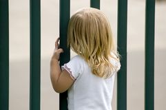 Waiting. Anxious little blond girl waiting at the gate for her mother royalty free stock image