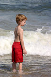 Waiting For It. A little boy with his eyes closed waiting for the wave to hit him Stock Photo