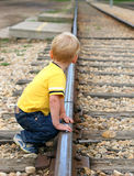 Waiting. Boy in yellow shirt watches down track, waiting for train stock image