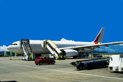 Waiting airplane on airport. The big airplane (jet) is connected with ladders and waiting on the airport. The airport technical and supporting staff is in Royalty Free Stock Images