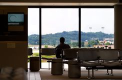 Waiting at airport. A man sits in a chair at the airport wiaitng for someone Stock Photos