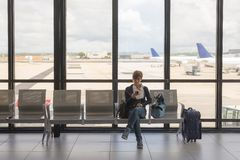Waiting in airport terminal using phone Stock Images