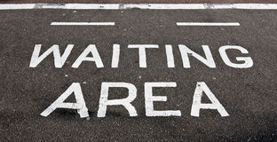 Waiting area. The words waiting area painted on tarmac on  a public footpath Royalty Free Stock Photos