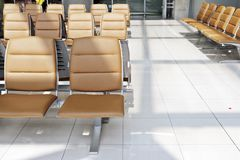 Waiting area before departure. Brown seats in airport waiting area for departure flight Stock Photo