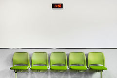 Waiting Area Green Seating. Row of green seating in a waiting area with neutral background Stock Image