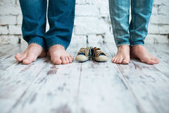 Waiting for the baby. Children`s shoes with the feet of parents.  Stock Photography