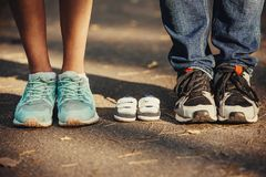 Waiting of baby. Little booties, sneakers near the feet of my father and mother. Pregnant woman, pregnancy, motherhood