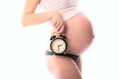 Waiting for the baby,  pregnant woman's belly   with  clock, whi Royalty Free Stock Photo