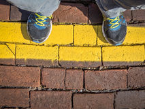 Waiting behind a yellow line Stock Photography