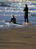 Waiting for the big one. Two surfers on the beach waiting for the right wave Royalty Free Stock Images