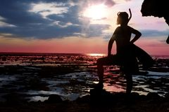 Waiting for big water. Woman standing during the low tide with diving equipment  on the shore and waiting for big water in sunset Stock Images