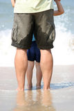 Waiting for the big wave. Legs of father and young son on a sandy beach waiting of the next wave Royalty Free Stock Photos