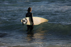 Waiting for a big wave. A surfer with his surfboard at the beach Royalty Free Stock Images