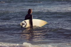 Waiting for a big wave. A surfer with his surfboard at the beach Stock Images